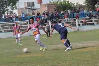 Hernán Rivero lleva el balón, mientras Maximiliano Taboada lo observa. Detrás, Saulo Reveco, José Luis Sosa y  la hinchada Azul Foto, gentileza de Javier Fernández-.